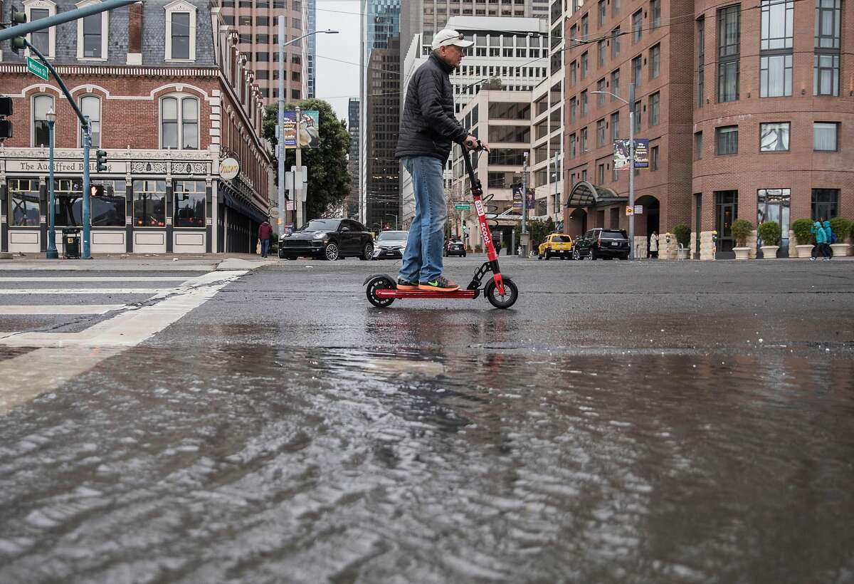 A man on an electric scooter rides past flood waters caused by large waves crashing into Pier 14 along the Embarcadero in San Francisco, Calif. Saturday, Jan. 5, 2019 as a winter storm moves through the Bay Area.