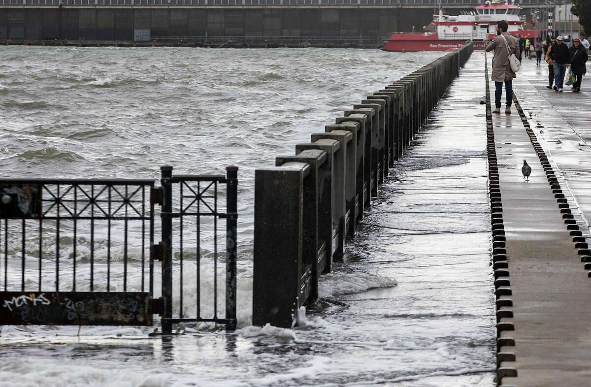 Pedestrians stop to take pictures as large waves crash into Pier 14 along the Embarcadero in San Francisco in January 2019. Light flooding is expected in the Bay Area on Sunday as king tides arrive.