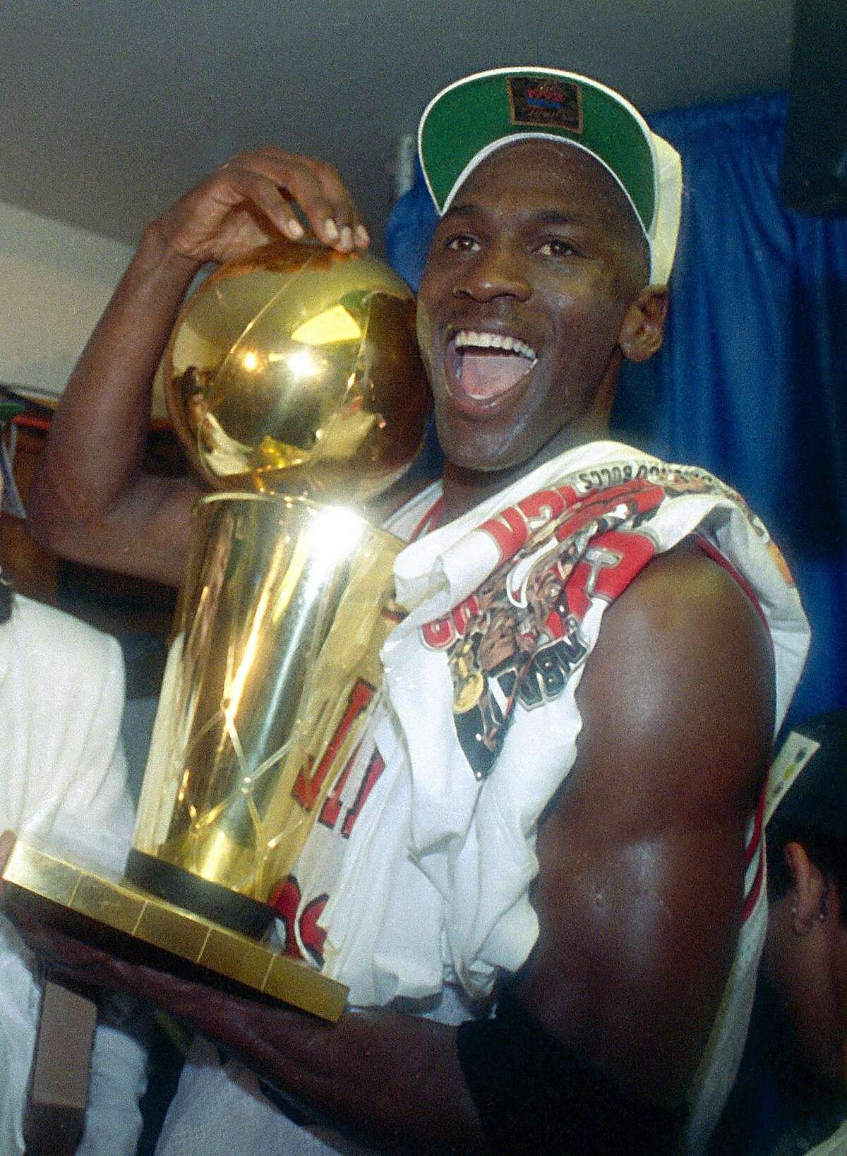 This is a june 14, 1992 file photo showing Chicago Bulls' Michael Jordan celebrating with the NBA trophy after the Bulls beat the Portland Trail Blazers 97-93 in Chicago, to win their second straight NBA title. On Friday, Sept. 11, 2009, Jordan will be enshrined at the Basketball Hall of Fame. (AP Photo/Mark Duncan, File)