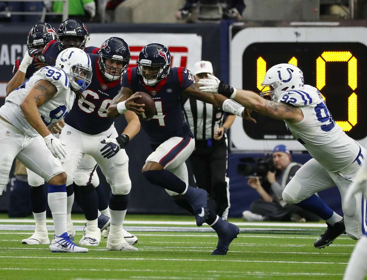 Houston Texans quarterback Deshaun Watson (4) tries to evade a tackle from Indianapolis Colts defensive end Margus Hunt (92) during the second quarter of an NFL first round playoff game at NRG Stadium, Saturday, Jan. 5, 2019, in Houston.