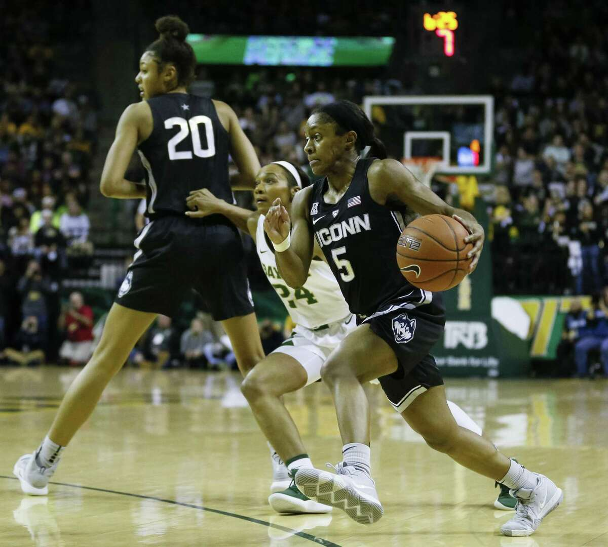 UConn guard Crystal Dangerfield works her away around Baylor guard Chloe Jackson (24) as forward Olivia Nelson-Ododa (20) sets the screen during the first half on Thursday.