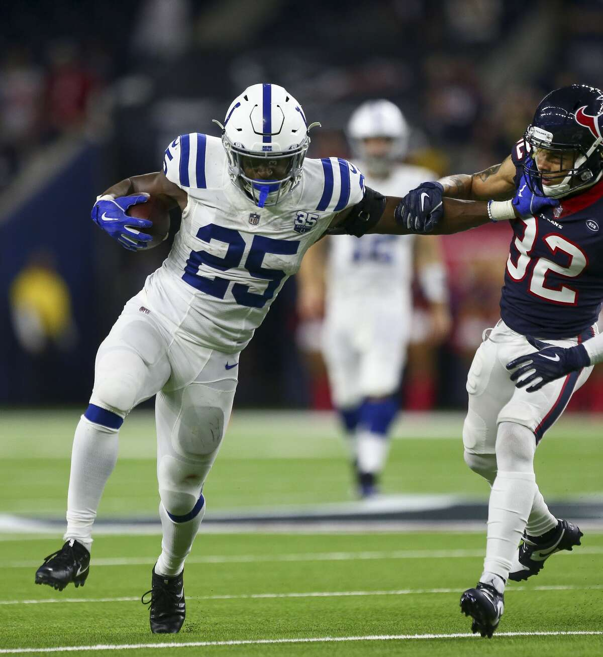 Indianapolis Colts running back Marlon Mack (25) stiff arms Houston Texans free safety Tyrann Mathieu (32) while running the ball during the fourth quarter of an NFL first round playoff game between the Houston Texans and the Indianapolis Colts at NRG Stadium Saturday, Jan. 5, 2019, in Houston. The Colts won 21-7.