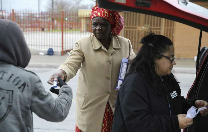 Redeemer's Praise Church's Pastor Shetigho Agbuke (center) hands a package of cookies to go with a meal to an individual near Houston and Frio Streets on Saturday, Dec. 29, 2018. Church groups and community members pooled their resources to help renovate Redeemer's Praise Church, where Agbuke and volunteers feed the homeless and parishioners living in poverty. (Kin Man Hui/San Antonio Express-News)