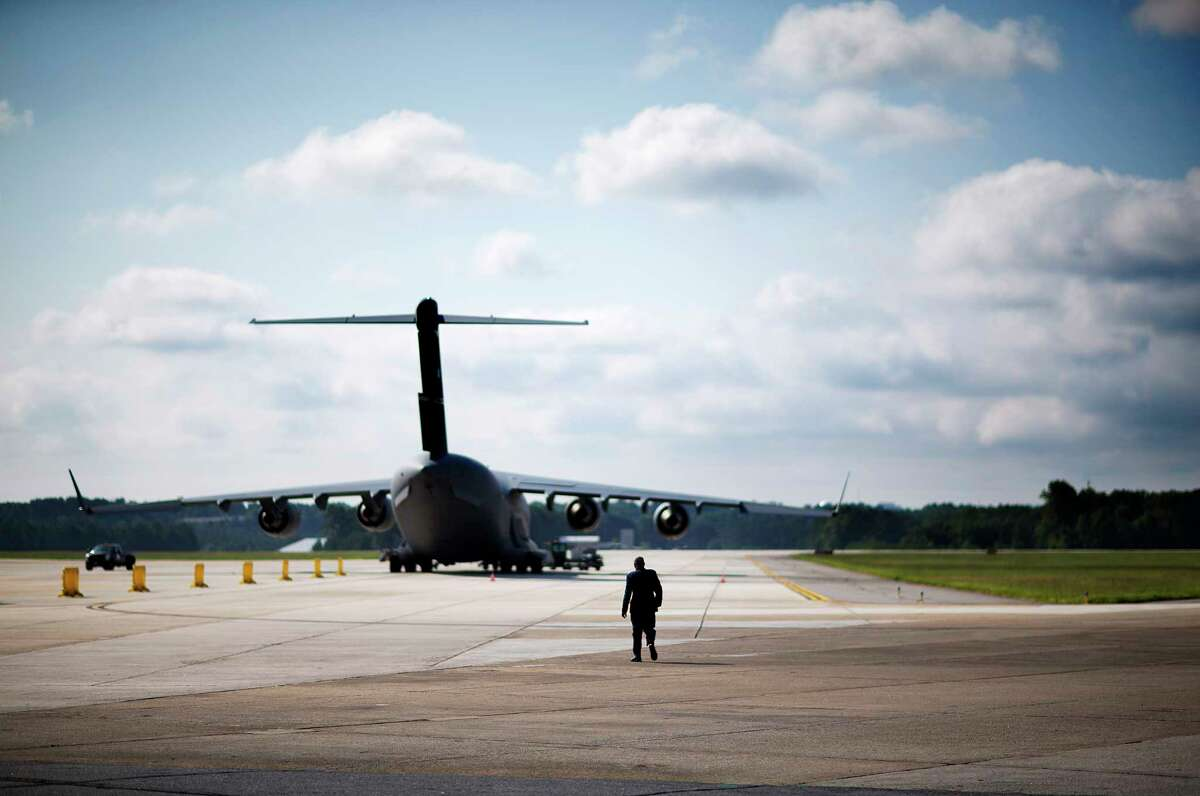 FILE - In an Aug. 11, 2015 file photo, n Air Force military member walks out to medevac biocontainment unit aboard a C-17 military transport plane at Dobbins Air Force Reserve Base during a media tour, in Marietta, Ga. There are fears that groundwater near Georgia military bases could remain contaminated from a toxic firefighting foam used for decades by the U.S. Air Force. Recent tests at Georgia's three air bases show extensive environmental contamination of groundwater. (AP Photo/David Goldman, File)