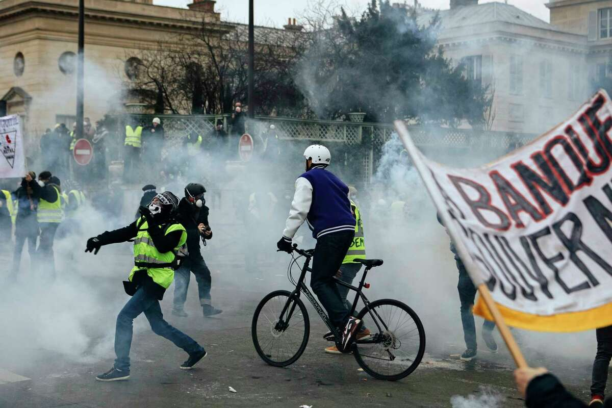 Demonstrators stand in tear gas thrown by riot police during a protest in Paris, Saturday, Jan. 5, 2019. Hundreds of protesters were trying to breathe new life into France's apparently waning yellow vest movement with marches in Paris and gatherings in other cities. (AP Photo/Kamil Zihnioglu)