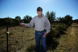 Henry Sauer stands near a fence line to show where a pipeline would potentially cross onto his property.
