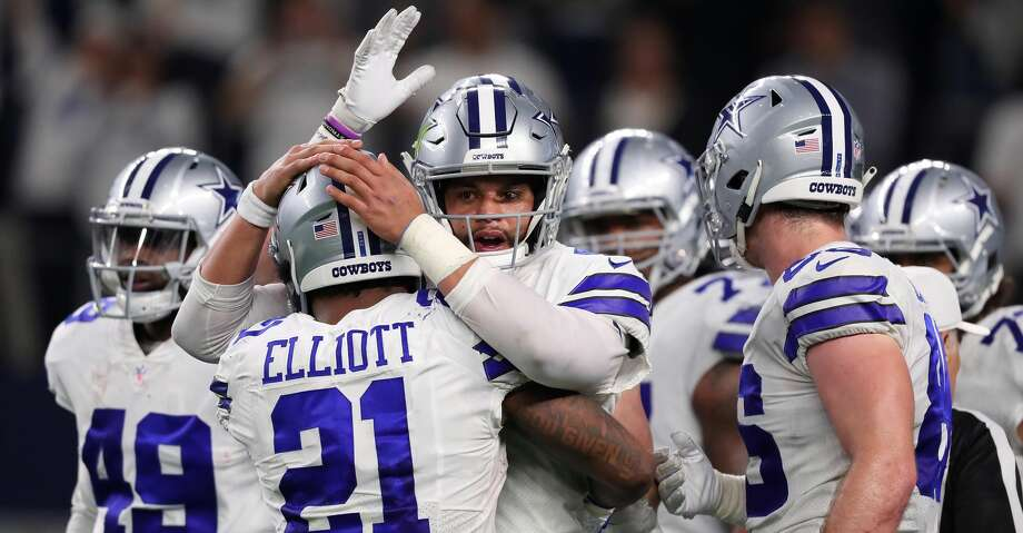 ARLINGTON, TEXAS - JANUARY 05: Ezekiel Elliott #21 of the Dallas Cowboys gets a hug from Dak Prescott #4 of the Dallas Cowboys after a fourth quarter touchdown against the Seattle Seahawks during the Wild Card Round at AT&T Stadium on January 05, 2019 in Arlington, Texas. (Photo by Tom Pennington/Getty Images) Photo: Tom Pennington/Getty Images