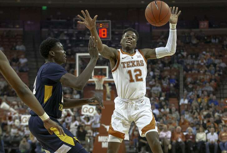 Texas guard Kerwin Roach II, right, loses control of the ball against West Virginia forward Wesley Harris. But the Longhorns remained in control throughout to down the Mountaineers.