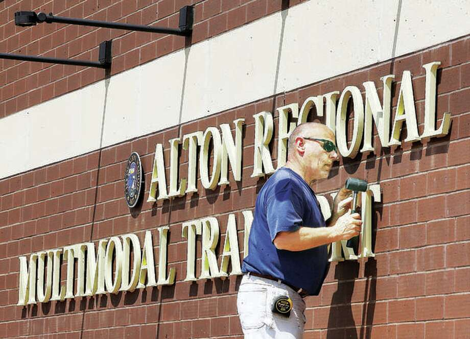 An employee of R.W. Boeker Co., Inc., in Hamel, uses a rubber mallet to tap a T into place for the lettering of the sign on the Alton Regional Multimodal Transportation Center. Photo: John Badman | The Telegraph