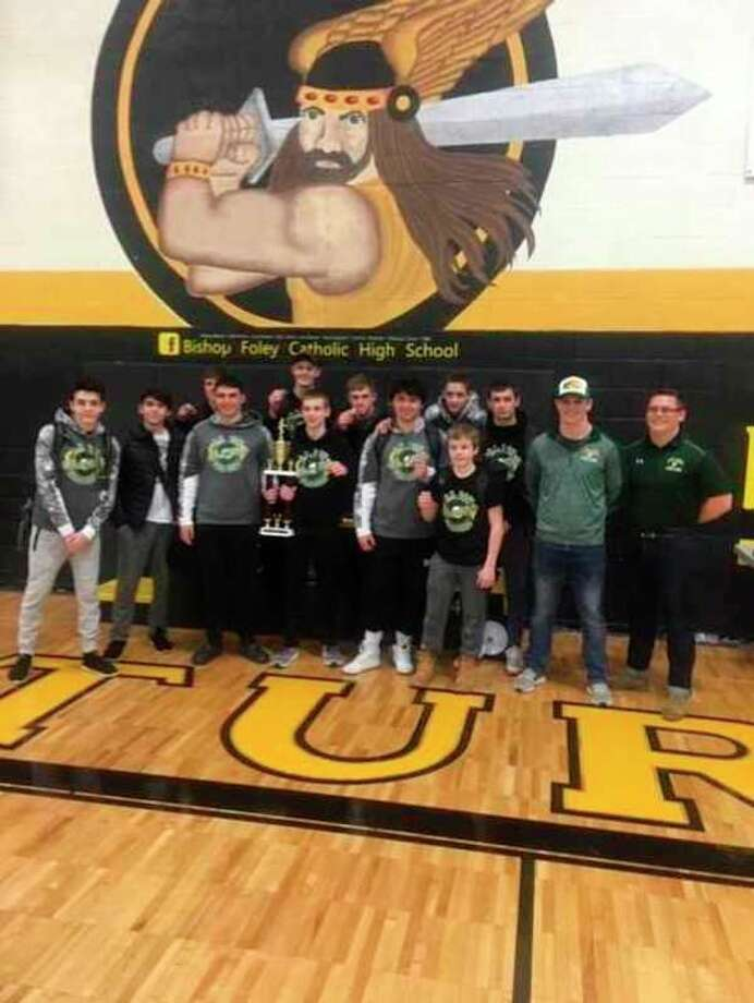 Dow High wrestlers stand with the team trophy after winning the Madison Heights Bishop Foley tournament on Saturday.