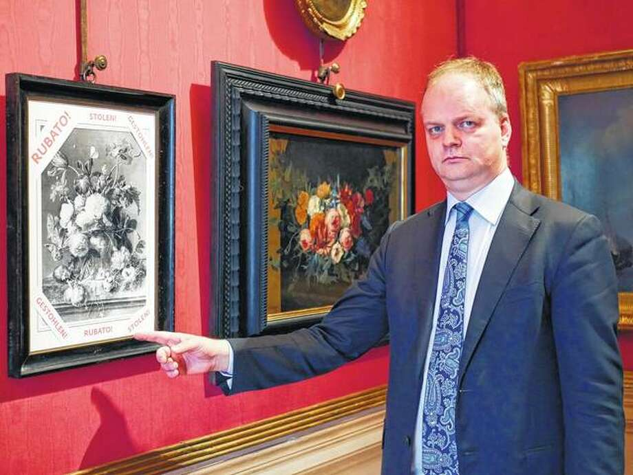 """Eike Schmidt, director of the Uffizi Gallery, points to a copy of a still-life """"Vase of Flowers"""", by Dutch artist Jan van Huysum, with writing in red reading """"stolen"""", at the Uffizi in Florence, Italy. Schmidt is urging Germany to return the Dutch masterpiece stolen by the Nazi troops during World War II, which is in the hands of a German family who hasn't returned it despite numerous appeals. Photo: Uffizi Gallery Press Office Via AP"""