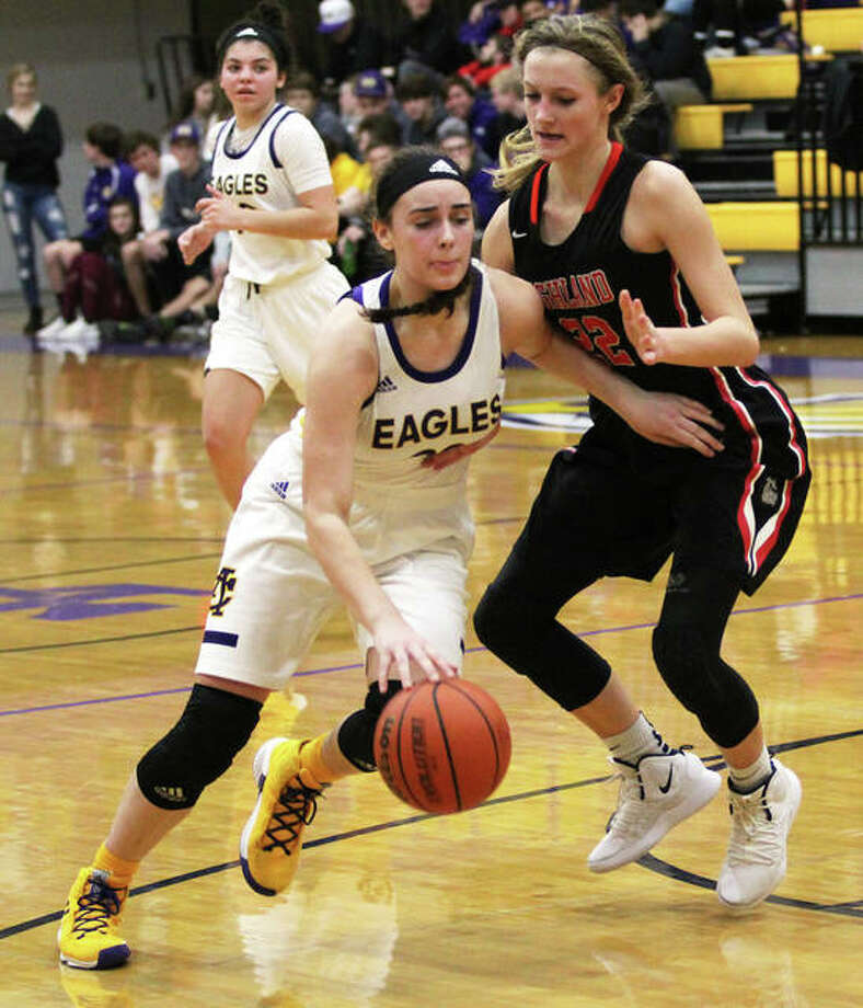 CM's Anna Hall (left), shown driving on Highland's Ashlyn Klucker in a Dec. 20 game in Bethalto, had a double-double Saturday in the Eagles' loss to O'Fallon at the Breese Central Shootout. Photo: Greg Shashack / The Telegraph