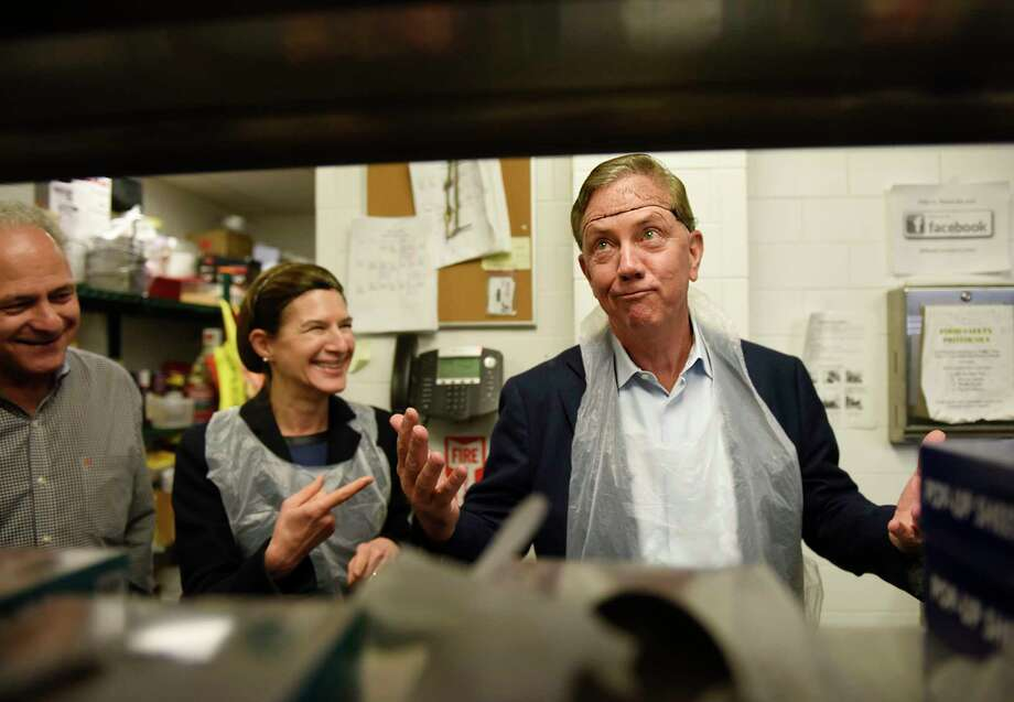 Connecticut Governor-elect Ned Lamont, right, reacts after putting on a hairnet to prepare food with Lieutenant Governor-elect Susan Bysiewicz, center, and New Covenant Center Executive Director John Gutman, left, at the New Covenant Center soup kitchen in Stamford, Conn. Sunday, Jan. 6, 2019. Connecticut Governor-elect Ned Lamont and Lieutenant Governor-elect Susan Bysiewicz visited Catholic Charities of Fairfield County's New Covenant Center in Stamford on Sunday as part of the five-stop Day of Service throughout the state. Lamont chose the 40-year-old food insecurity program in Stamford to recognize the organization for providing more than 600,000 meals each year through its 365-day-a-year soup kitchen and three-day-a-week food pantry. Photo: Tyler Sizemore, Hearst Connecticut Media / Greenwich Time