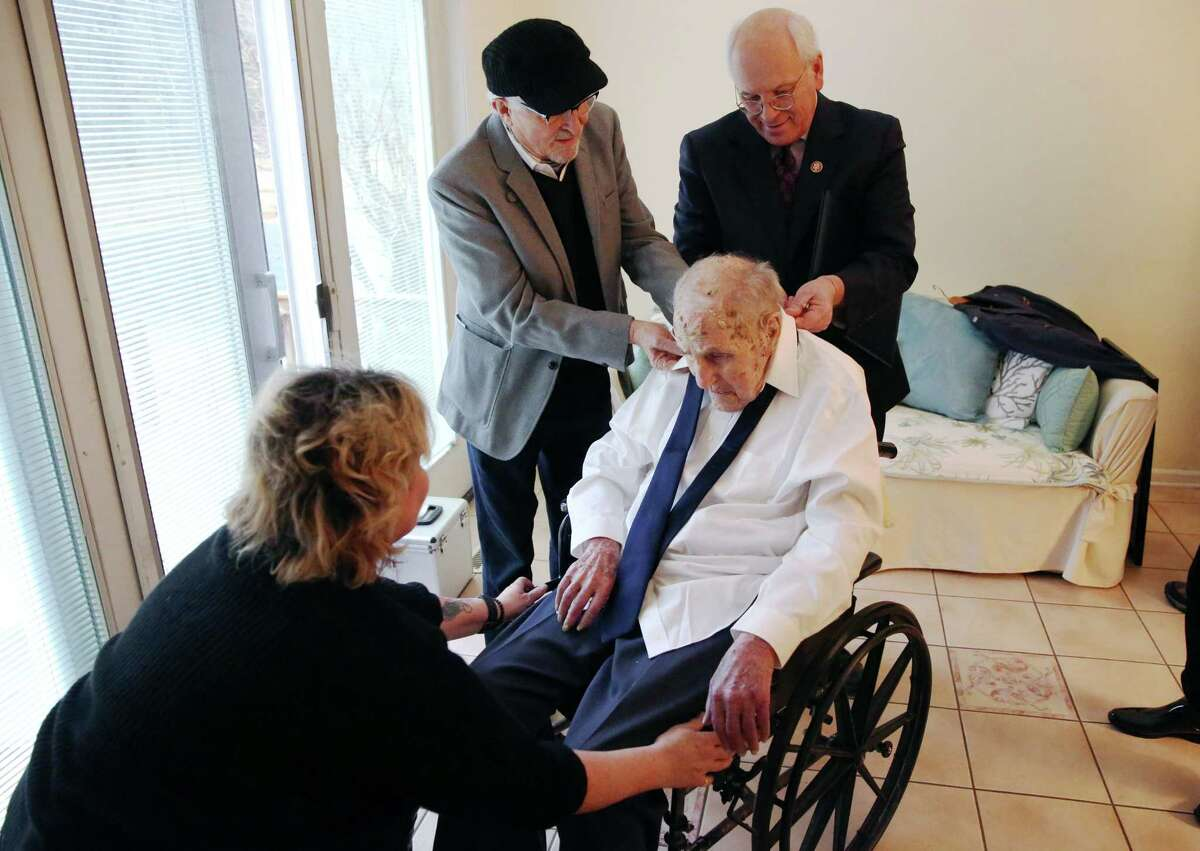 Congressman Paul Tonko and Jean Claude Simille help World War II Army Air Forces veteran Robert Carlyn put his tie on before his promotion ceremony Saturday, Jan. 5, 2019 at Carlyn's home in Delmar, N.Y. (Phoebe Sheehan/Times Union)