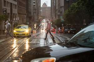 Pedestrians make their way over California Street as rain continued through the weekend in San Francisco on Sunday, January 6, 2019.