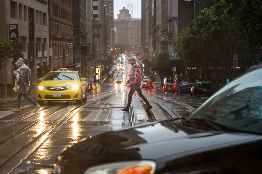 Pedestrians make their way over California Street as rain continued through the weekend in San Francisco on Sunday, January 6, 2019. Photo: Jana Asenbrennerova, Special To The Chronicle