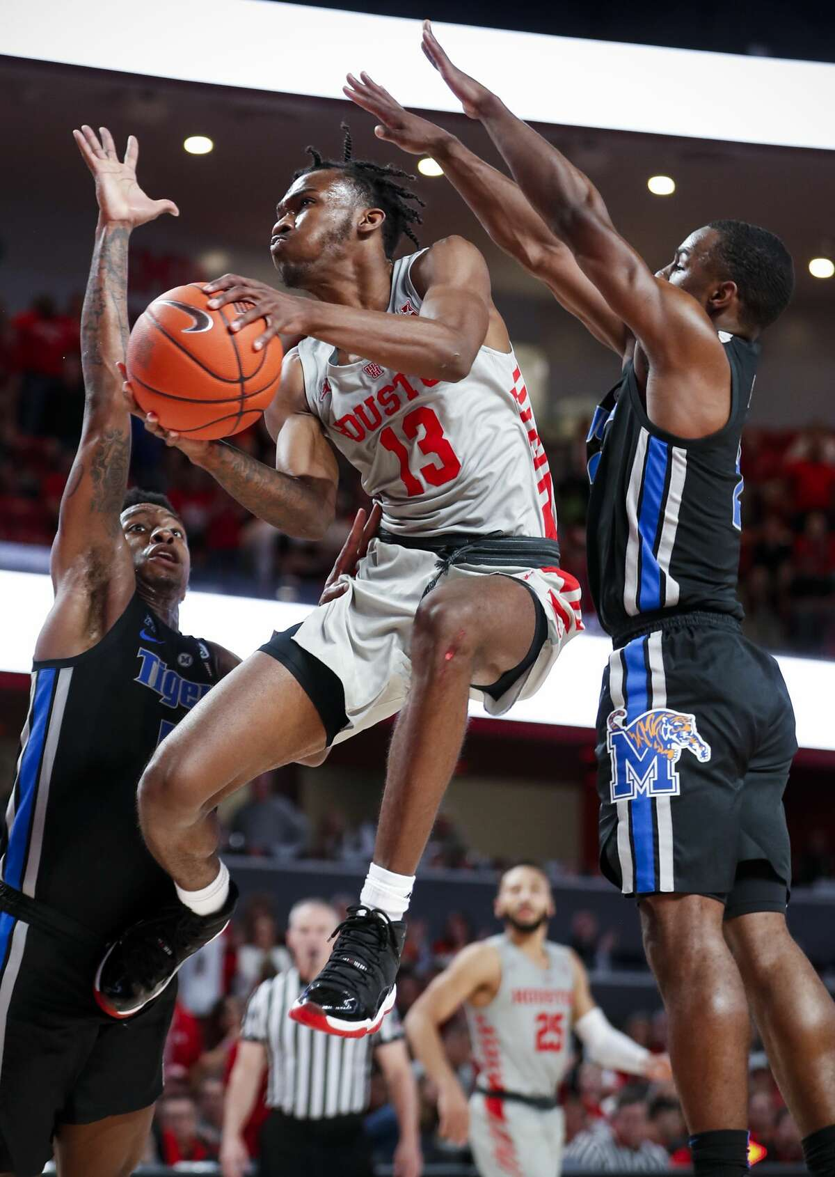 Houston guard Dejon Jarreau (13) drives to the basket between Memphis guards Kareem Brewton Jr. (5) and Alex Lomax (2) during the second half on a NCAA basketball game at Fertitta Center on Sunday, Jan. 6, 2019, in Houston.