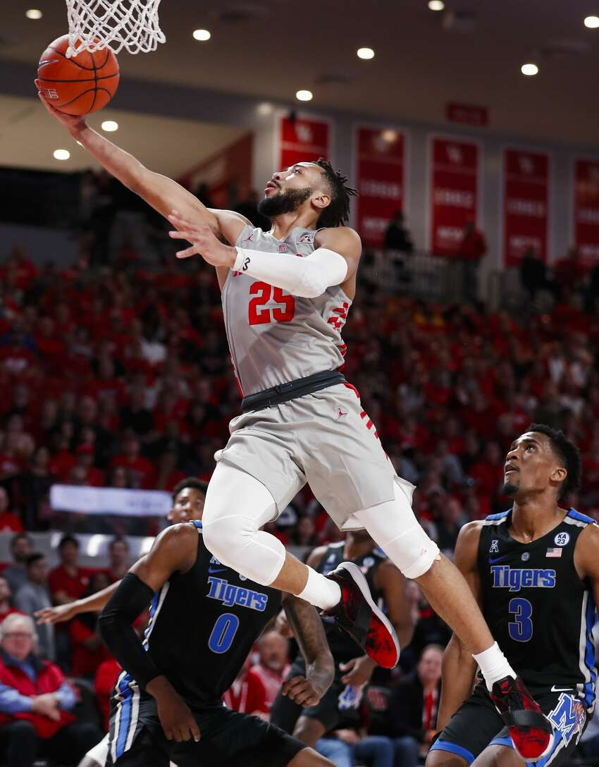 Houston guard Galen Robinson Jr. (25) takes the ball to the basket past Memphis guard Jeremiah Martin (3) and forward Kyvon Davenport (0) during the first half of an NCAA college basketball game Sunday, Jan. 6, 2019, in Houston. (Brett Coomer/Houston Chronicle via AP)