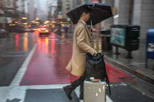 A pedestrian makes his way over Market Street as rain continued through the weekend in San Francisco on Sunday, January 6, 2019.