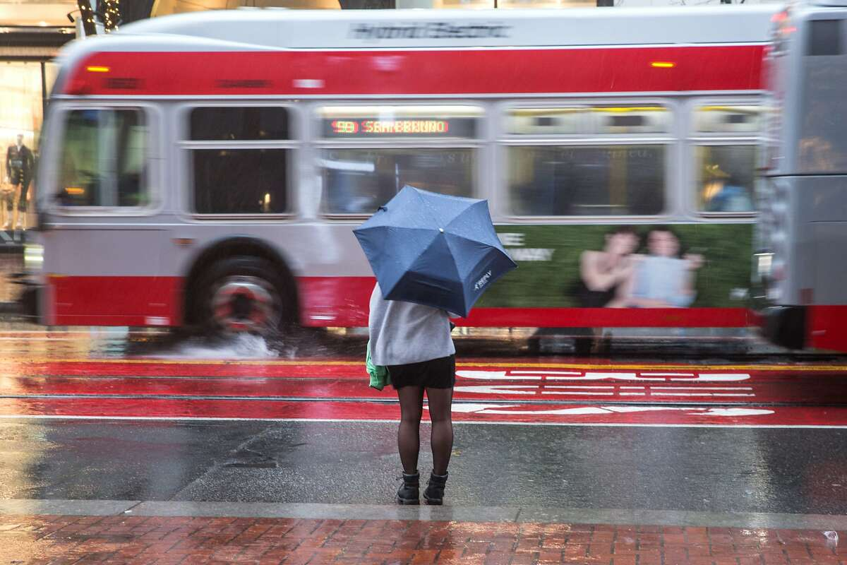 FILE PHOTO: A person stands along Market Street as rain continued through the weekend in San Francisco on Sunday, January 6, 2019.