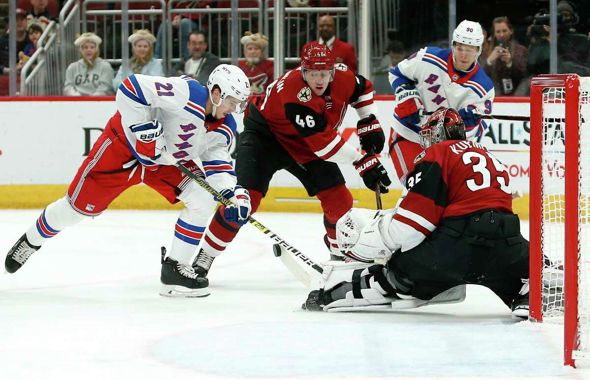 New York Rangers center Brett Howden (21) plays the puck in front of Arizona Coyotes goalie Darcy Kuemper (35) as Arizona Coyotes' Ilya Lyubushkin (46) defends during the first period of an NHL hockey game, Sunday, Jan. 6, 2019, in Glendale, Ariz. (AP Photo/Ralph Freso)