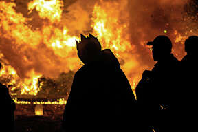 A powerful inferno signals the end of the Christmas season Sunday evening during the traditional Twelfth Night celebration in Alton's Haskell Park. Donations of live Christmas trees were welcomed to be used in a bonfire, bidding farewell to the holiday. The celebration includes long-held customs such as the offering of Apple Wassail to guests - a symbolic blessing to ensure a good harvest - which began in 1750. Twelfth Night also celebrates the eve of the Epiphany, the day that the story of the nativity has the Three Wise Men guided to the birth of Jesus, also symbolized in Haskell Park's celebration. One of the The Wise Men watches over the fire next to other guests Sunday night in Haskell Park during the tradition Twelfth Night celebration.