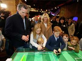 Governor-elect, Lt. Gov. Gavin Newsom, left, and his wife, Jennifer Siebel Newsom, center, watch last their children, daughter Montana, second from left, and sons, Dutch, foreground and Hunter, foreground fourth from left, operate robot games during an Inaugural Family Event at the California Railroad Museum, Sunday, Jan. 6, 2019,,Sacramento, Calif. Newsom will be sworn-in as California's 40th governor, Monday.  Jennifer Siebel Newsom