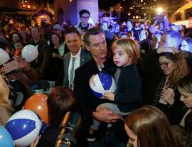Governor-elect, Lt. Gov. Gavin Newsom, carries his son, Dutch, through the crowd during a pre-inaugural Family Event at the California Railroad Museum, Sunday, Jan. 6, 2019, in Sacramento, Calif. Newsom will be sworn-in as California's 40th governor, Monday.