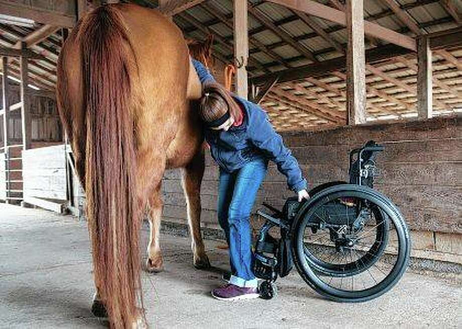 Sami Bayless steadies herself with her horse, Dunny, as she reaches for a brush in Lamar, Missouri. Bayless mounted her horse again more than six months after suffering injuries to her spine and legs during a car accident. Photo: Roger Nomer | Joplin Globe (AP)