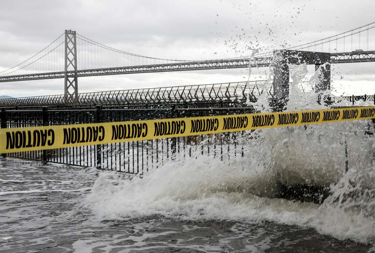 Caution tape is draped across Pier 14, closing it off to the public as large waves crash and cause flooding along the Embarcadero in San Francisco, Calif. Saturday, Jan. 5, 2019 as a winter storm moves through the Bay Area.