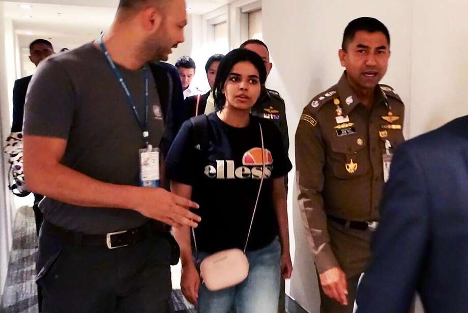 "This handout picture taken and released by Thai Immigration Bureau on January 7, 2019 shows 18-year-old Saudi woman Rahaf Mohammed al-Qanun (2nd-L) is being escorted by the Thai immigration officer and United Nations High Commissioner for Refugees (UNHCR) officials at the Suvarnabhumi international airport in Bangkok. - Rahaf Mohammed al-Qunun, seeking asylum has left Bangkok airport ""under the care"" of the UN refugee agency, a Thai official said Monday, following her desperate plea against deportation. (Photo by - / Thai Immigration Bureau / AFP)-/AFP/Getty Images Photo: -, AFP/Getty Images"