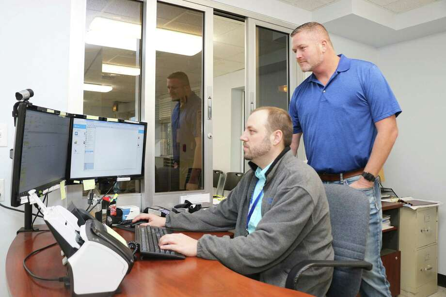 CEO Matt Thornton looks over the shoulder of Business Office Manager Matt Quinn as he uses the new software. The acquisition of the technology makes it possible for a paperless environment. Photo: David Taylor / HCN