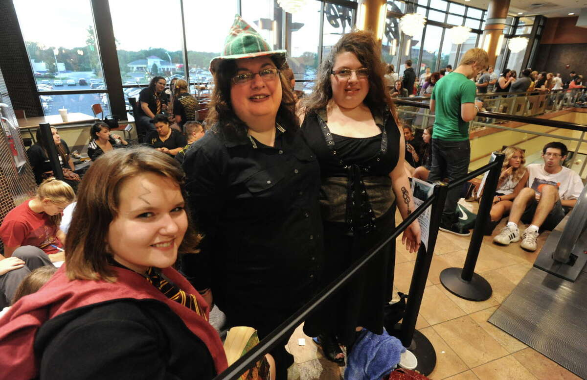 """Olivia Ugino, 17, of Latham, left, arrived at 8:30am and Cecelia Graves, 19, of Watervliet, right arrived at 6:30am on Thursday, July 14, 2011 to make sure they were the first in line to see the newest Harry Potter movie """"Harry Potter and the Deathly Hallows: Part 2 """" at Regal Cinemas at Colonie Center in Colonie, N.Y. Cecelia's mother Donna Graves, 43, of Cohoes, middle, joined her daughter after work at 6:00pm. (Lori Van Buren / Times Union)"""