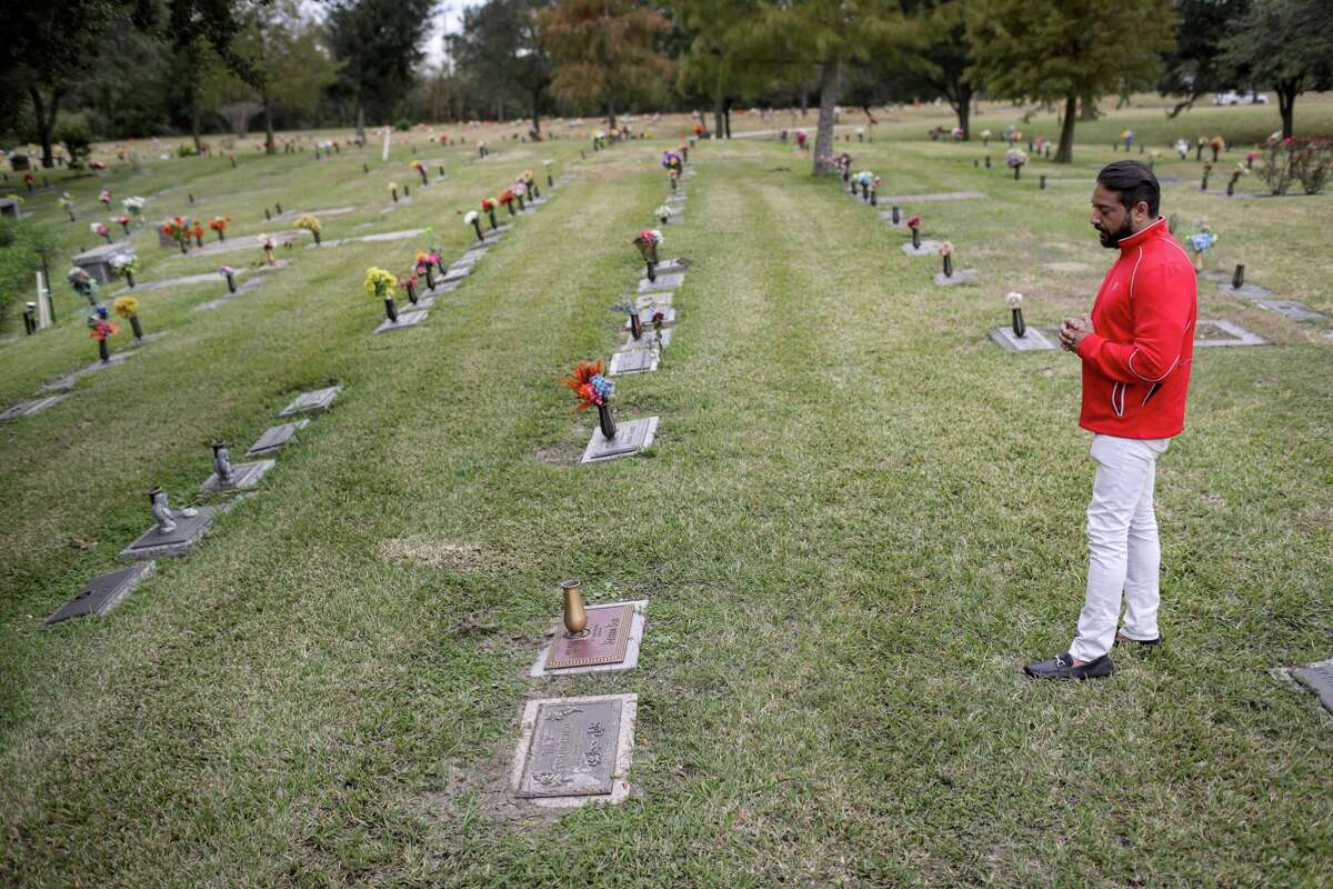 Yousuf Beg demonstrates how he prays at his father's grave at Forest Lawn Cemetery, Wednesday, Nov. 28, 2018, in Houston. Beg said that his father had no will when he died, which is a common occurrence in American-Muslim families.