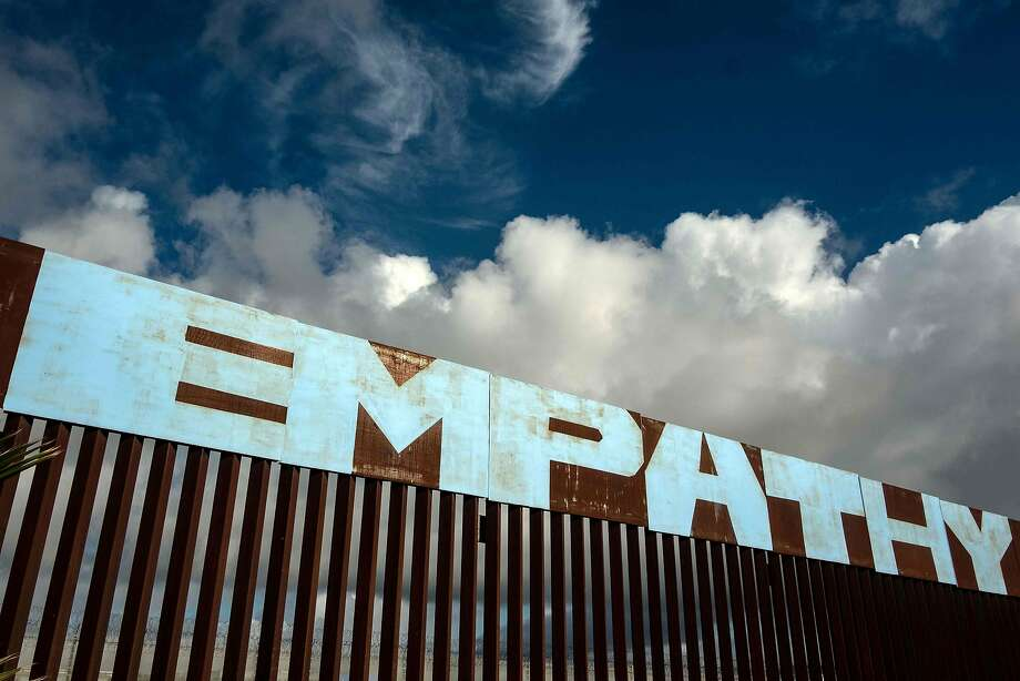 """An """"empathy"""" message appears on the Mexican side of the border fence at the Otay Mesa entry in San Diego. President Trump will visit the border Thursday. Photo: Guillermo Arias / AFP / Getty Images"""