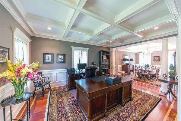 There is flexible room on the first floor that can be used as a formal living room or office with a coffered ceiling and wainscoting on the lower walls.