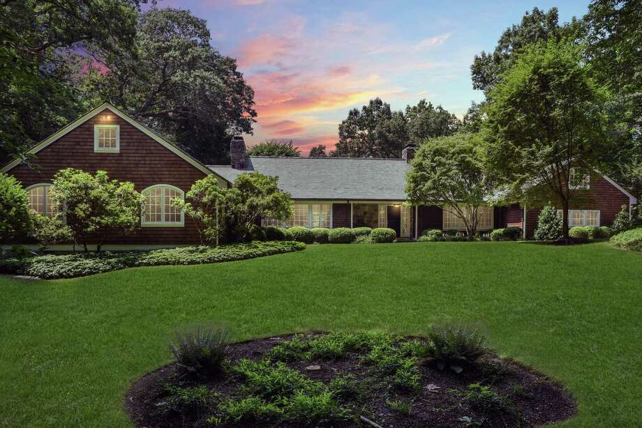 The brown shingle and stone house at 75 Louise's Lane sits on a property of almost three acres on a quiet cul-de-sac only two minutes from Scott's Corner and four miles from New Canaan Village.