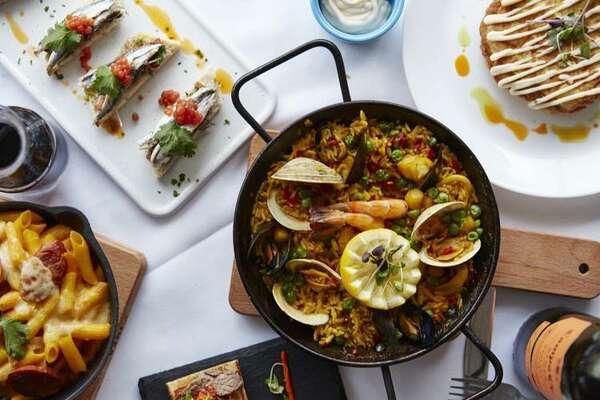 Some of the dishes at Gaudí Tapas and Wine in Danbury include paella(center),macarrons al forn(bottom left),pincho de boquerones(top left) andtortilla Española(top right).