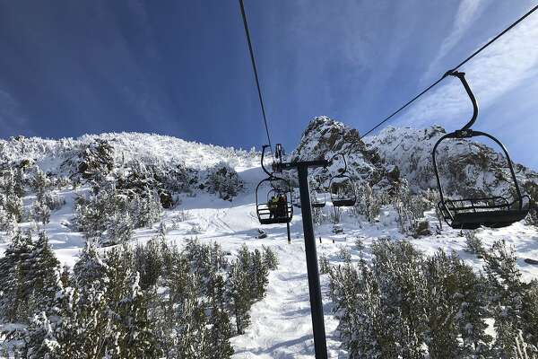 In this Friday, Dec. 7, 2018, skiers going up a lift at Mammoth Mountain ski resort in Mammoth Lakes, Calif. Back-to-back California storms have blanketed the Sierra Nevada in snow, pushing the snowpack to 106 percent above average, with winter still nearly two weeks away. (AP Photo/Christopher Weber)