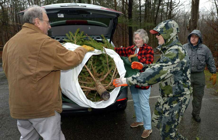 Wilton residents Chris and Beth Schellhorn unload their Christmas tree with the help of Trout Unlimited board member Rich Thibodeau and president Ben Coach for the Mianus Chapter of Trout Unlimited Trees for Trout Collection on Saturday, for volunteers at Merwin Meadows in Wilton. The trees turn into important habitat for wild trout in the Norwalk and Mianus rivers. Each tree will join hundreds of others in helping stabilize stream banks, reduce erosion and create refuge habitat for juvenile trout and other aquatic life. Photo: Erik Trautmann / Hearst Connecticut Media / Norwalk Hour