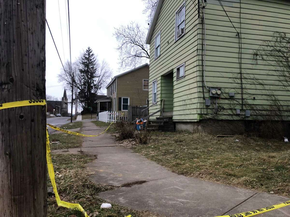 Police remain on the scene Monday, Jan. 7, 2019, of a homicide on Lincoln Avenue in Utica, N.Y. An off-duty Albany police officer is accused of