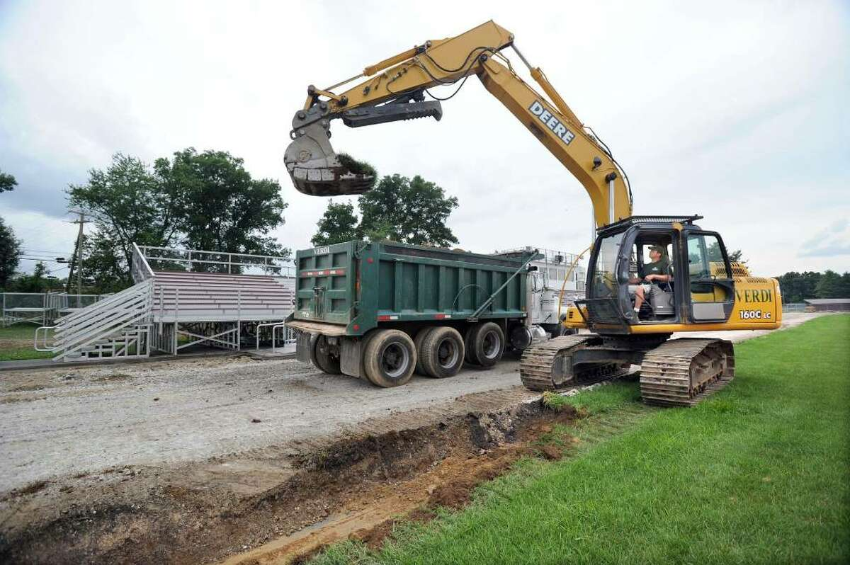 Doug Verdi of Verdi Construction in Bethel runs the backhoe during work on renovations to the Bethel High School track Tuesday, July 20, 2010. Doug works with his brother, Curt, owner of the company. Both brothers are Bethel High School graduates. The renovations include changing the track from six to eight lanes.
