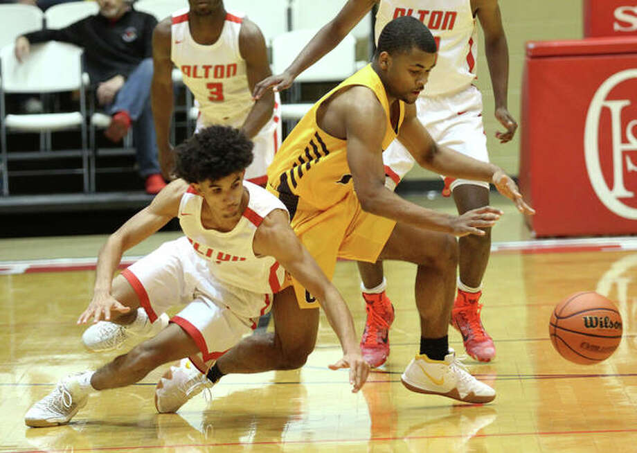 Alton's Andrew Jones (left) goes to the floor after tipping the ball away from a Mundelein Carmel player during the Redbirds' first-round win Dec. 27 at the Centralia Holiday Tournament. Photo: Greg Shashack / The Telegraph