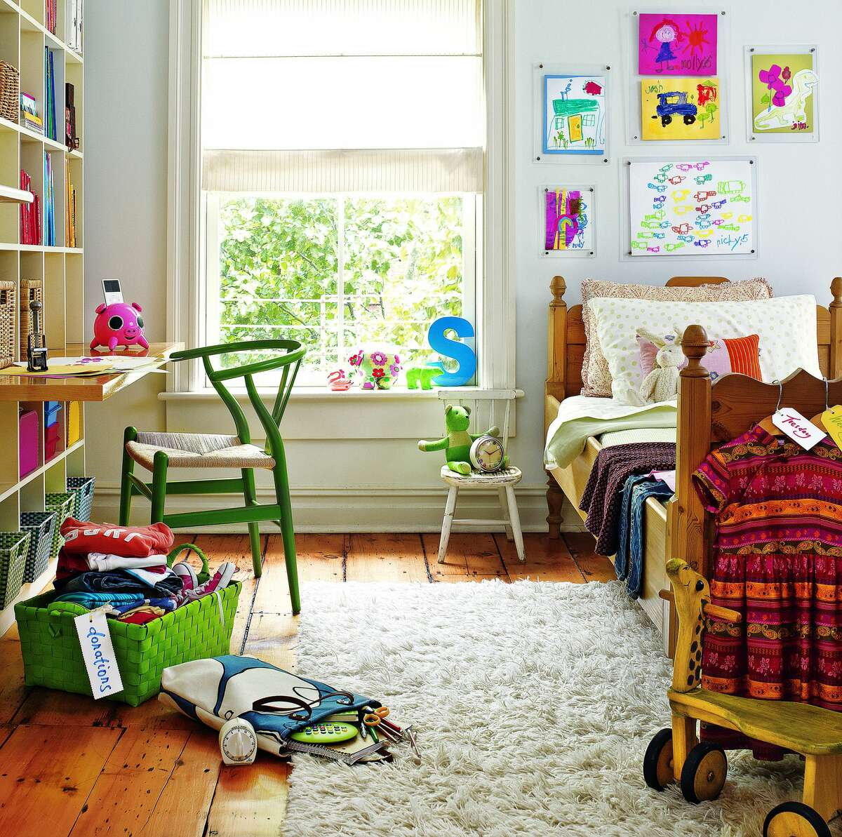 """A wall of storage bins in a child's room teaches your kids the responsibility of picking up after themselves. If getting rid of clutter and having a tidier or more organized home is a goal for 2019, Real Simple's new""""The Real Simple Method to Organizing Every Room"""" book offers plenty of advice."""