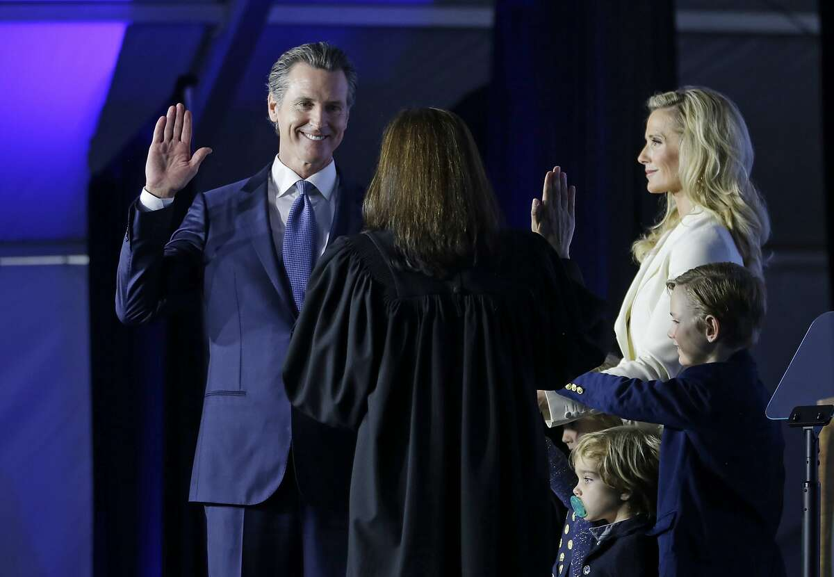 California Governor Gavin Newsom takes the oath of office from state Supreme Court Chief Justice Tani Gorre Cantil-Sakauye during his inauguration Monday, Jan. 7, 2019, in Sacramento, Calif. Looking on is Newsom's wife, Jennifer Siebel Newsom and their sons, Dutch, second from right, and Hunter, right. (AP Photo/Rich Pedroncelli)