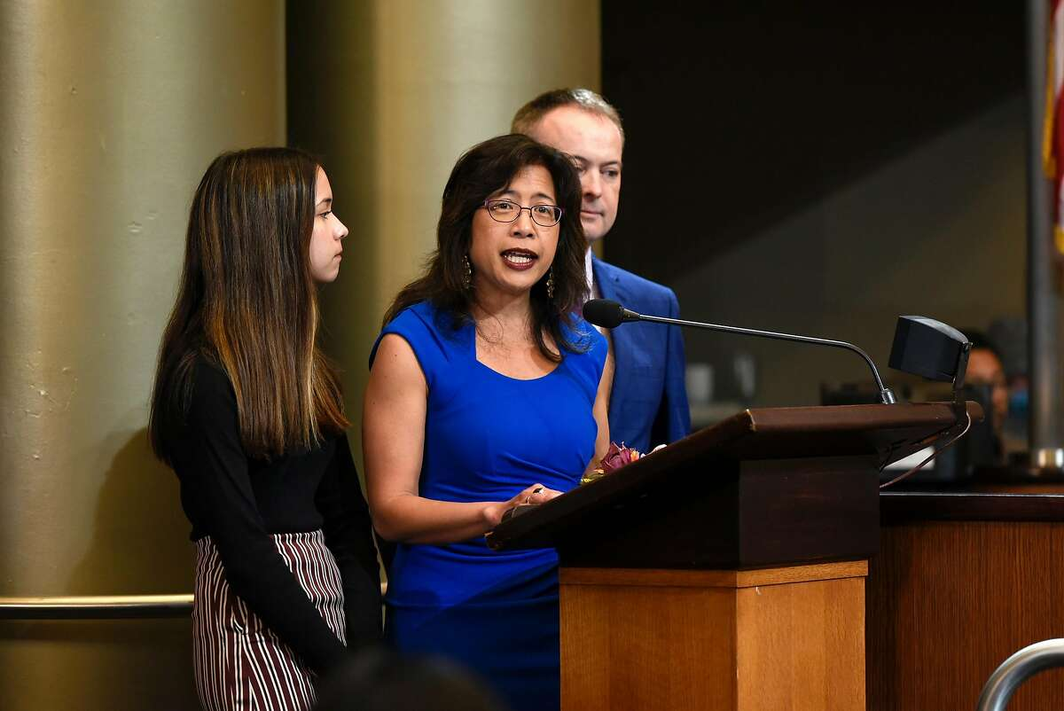 Oakland City Council member Nikki Fortunato Bas gives a speech flanked by her daughter Velana and husband Brad after being sworn in during an inauguration ceremony for elected representatives at City Hall in Oakland, Calif., on Monday, January 7, 2019.