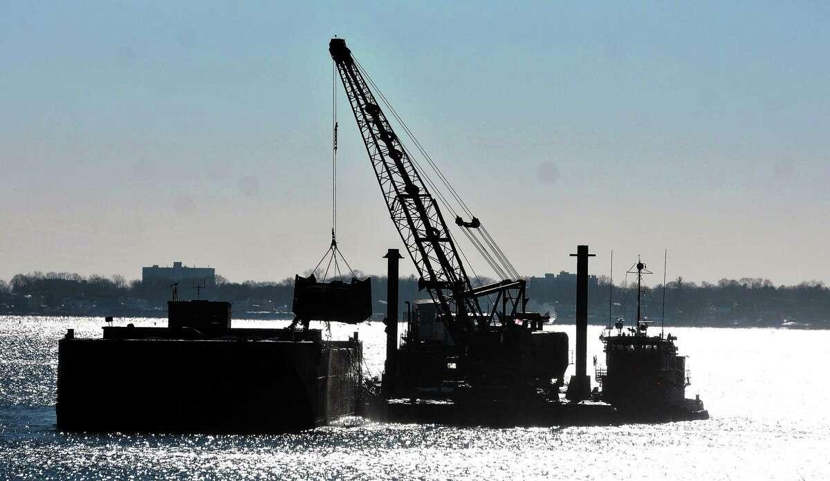 A dredger removes sediment from New Haven Harbor near the Pearl Harbor Memorial Bridge in 2014.
