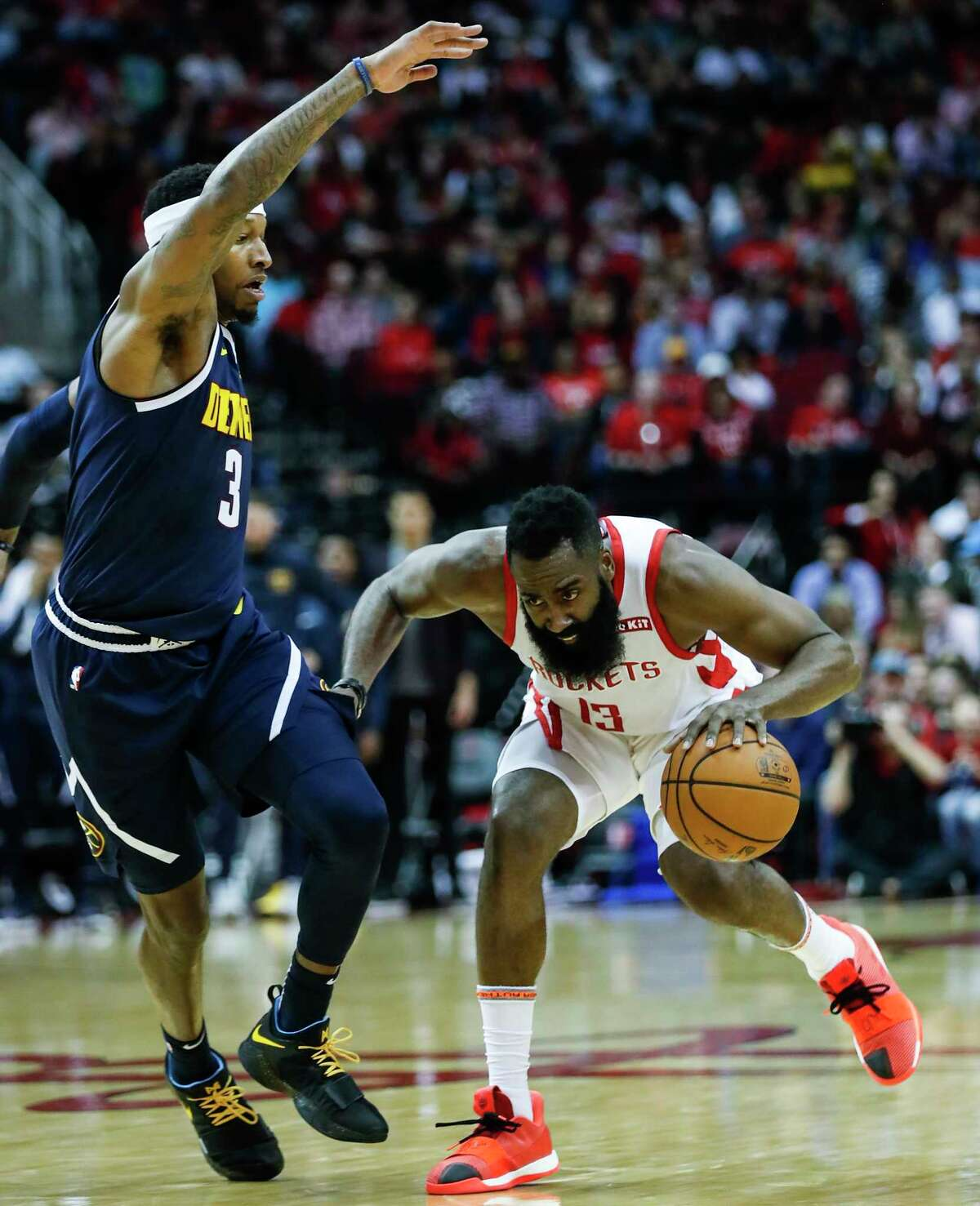 Houston Rockets guard James Harden (13) works against Denver Nuggets forward Torrey Craig (3) as he brings the ball up the court during the first half of an NBA basketball game at Toyota Center on Monday, Jan. 7, 2019, in Houston.