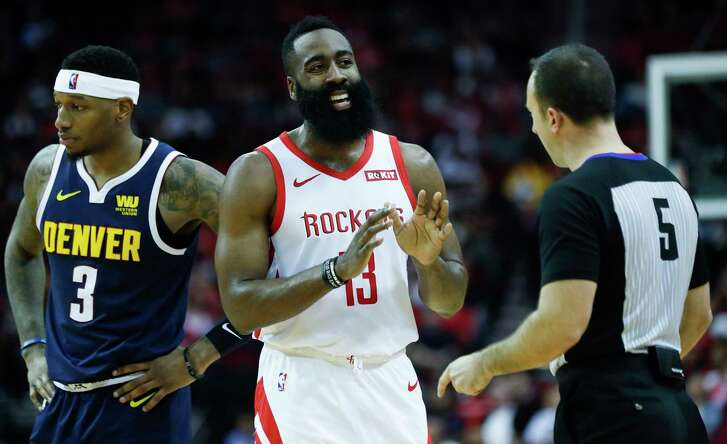 Houston Rockets guard James Harden (13) talks to referee Kane Fitzgerald (5) during the first half of an NBA basketball game against the Denver Nuggets at Toyota Center on Monday, Jan. 7, 2019, in Houston. Denver Nuggets guard Will Barton (5) is standing next to Harden.