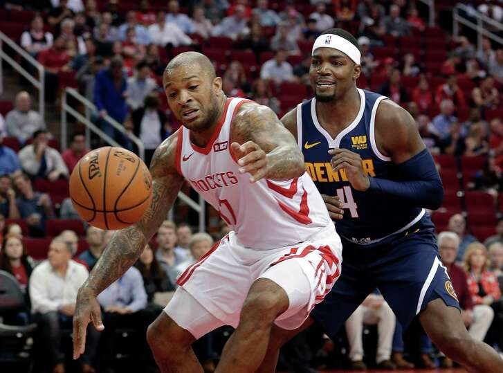 Houston Rockets forward PJ Tucker (17) reaches to recover the ball after it was knocked away by Denver Nuggets forward Paul Millsap (4) during the first half of an NBA basketball game Monday, Jan. 7, 2019, in Houston. (AP Photo/Michael Wyke)